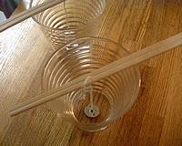 ミツロウキャンドルの作り方・1・ヒモ(火芯)の準備・2つに割っていない割り箸にヒモを通して、コップにちょうどよい長さに垂らしておきます。